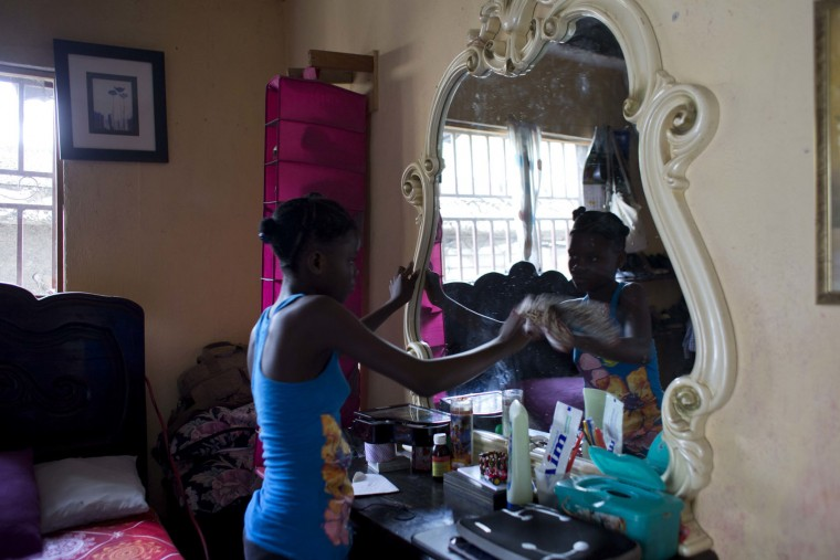 In this May 27, 2017 photo, 13-year-old Medege Dorlus cleans a mirror at the home she lives in, in Port-au-Prince, Haiti. Meddle goes to school in the morning and then comes back to clean and take care of the household. (AP Photo/Dieu Nalio Chery)