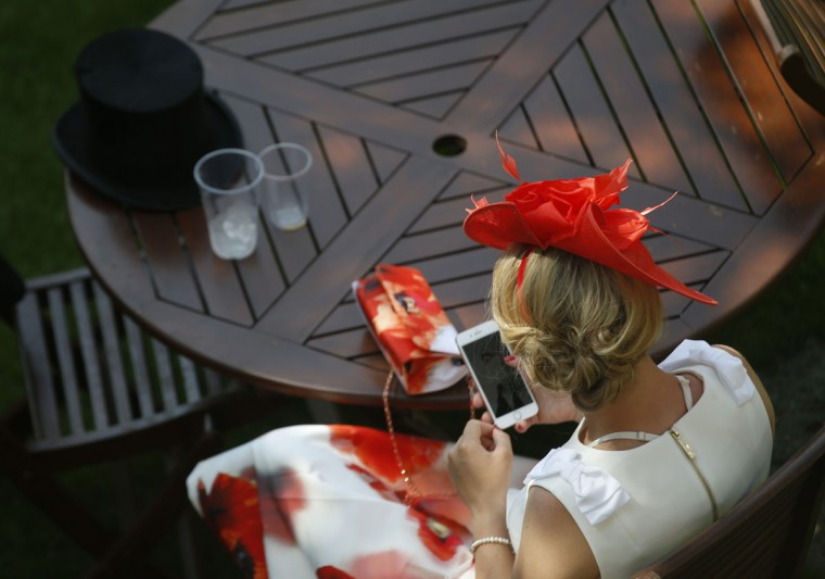 A woman looks at her smart phone in a quiet corner on the first day of the Royal Ascot horse race meeting in Ascot, England, Tuesday, June 20, 2017. (AP Photo/Alastair Grant)