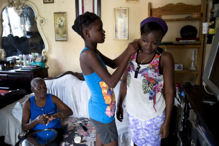 "In this May 27, 2017 photo, 13-year-old Medege Dorlus, center, helps Stephanie, the daughter of Marie Roseline, the lady of the house, with an earring, as Marie Roseline looks on at their home in Port-au-Prince, Haiti. Medege lives with five members of the family that took her in when her mother died, but ""Living with your mom isn't the same as living with your extended family"" she said. (AP Photo/Dieu Nalio Chery)"