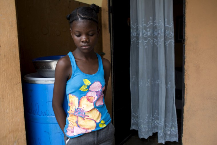 "In this May 27, 2017 photo, 13-year-old Medege Dorlus nods off as she stands inside the home of friends of her late mother who took her in as an unpaid servant or ""restavek,"" in Port-au-Prince, Haiti. ""Restavek"" is a practice deeply ingrained in Haiti, where families frequently have numerous kids despite crushing poverty. (AP Photo/Dieu Nalio Chery)"