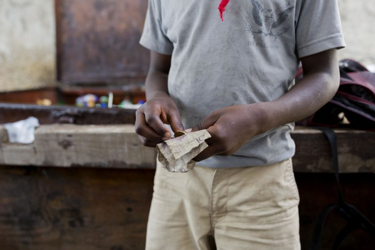 "In this May 23, 2017 photo, 12-year-old Watson Saint Fleur counts his money before going out to buy water bags he sells on the streets of Petion-Ville, a suburb of Port-au-Prince, Haiti. Watson is a ""restavek,"" a term to describe children whose poor parents hand them over to others. Now he lives at a woman's house but he's fuzzy about how he ended up at her house, only knowing his mother died in his hometown of Petit Goave. He never knew his father. (AP Photo/Dieu Nalio Chery)"