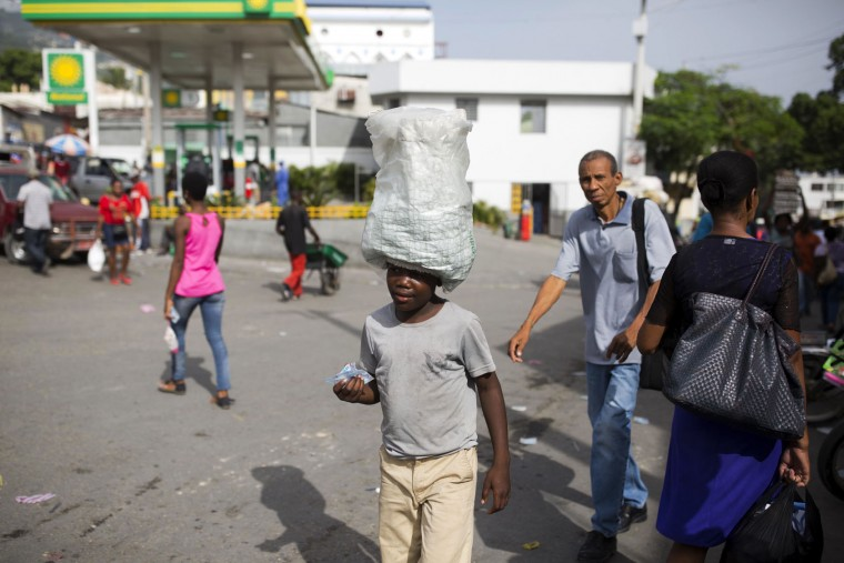 "In this May 23, 2017 photo, 12-year-old Watson Saint Fleur balances water packets on his head as he sells them in the streets of Petion-Ville, a suburb of Port-au-Prince, Haiti. Watson is a ""restaveks,"" a term to describe children whose poor parents hand them over to others. Their numbers have been growing sharply as urban slums expand and poverty in the countryside deepens. (AP Photo/Dieu Nalio Chery)"