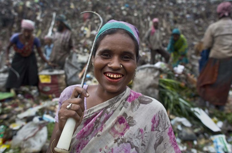 Sanuwara Beghum, an Indian ragpicker woman smiles to the camera as she looks for recyclable material at a garbage dumping site on the outskirts of Gauhati, Assam state, India, Monday, June 5, 2017. Monday marks World Environment Day. (AP Photo/Anupam Nath)