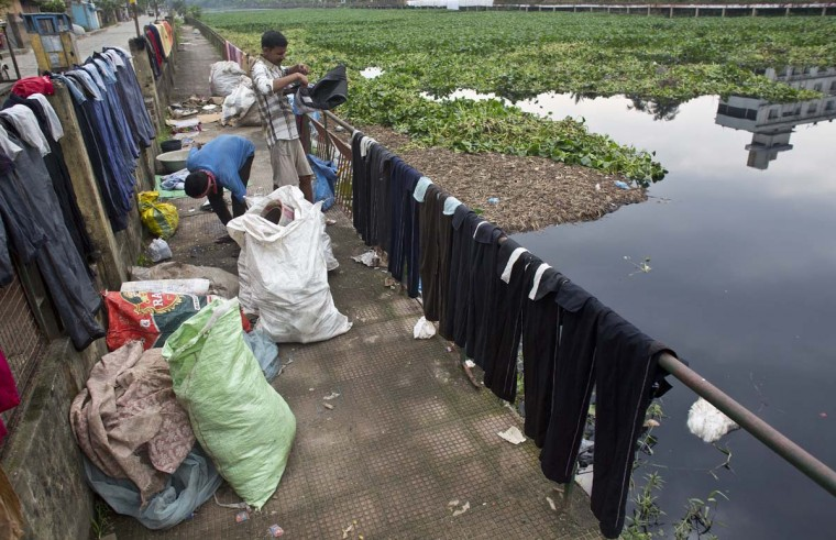 Indian laundry workers dry clothes near a polluted pond on World Environment Day in Gauhati, India, Monday, June 5, 2017. (AP Photo/ Anupam Nath)