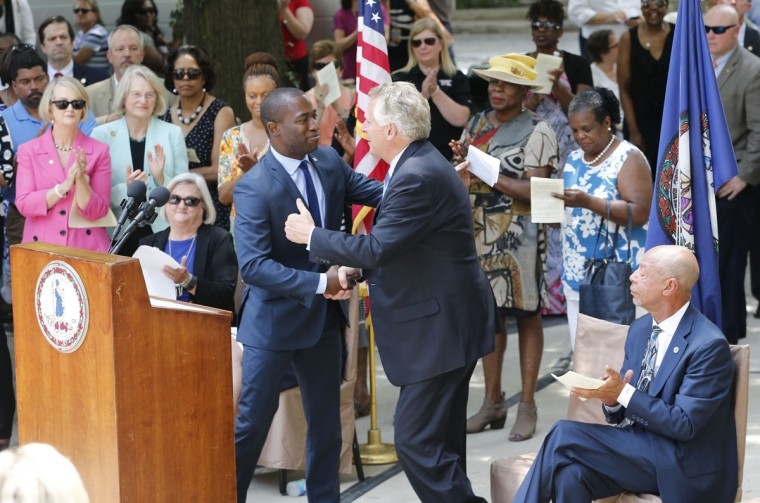 Virginia Gov. Terry Mcauliffe, center right, shakes hands with with Richmond mayor, Levar Stoney, center left, during a ceremony to unveil a historical marker commemorating the 50th anniversary of the U.S. Supreme Court decision that struck down bans on interracial marriage Monday, June 12, 2017, in Richmond, Va. The new historical marker to commemorate the lawsuit brought by Richard and Mildred Loving, was dedicated outside the old Virginia Supreme Court, which ruled against the Lovings before they ultimately won in the U.S. Supreme Court. (AP Photo/Steve Helber)