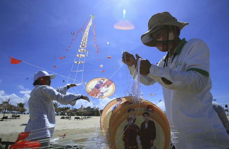 In this Sunday, June 11, 2017 photo, kite makers fly a dragon kite on Tam Thanh beach during an International Kite Festival in Quang Nam province, Vietnam. Hundreds of flying giant sea creatures, animal shaped and folklore inspired kites from 20 countries were taken to the sky. (AP Photo/Hau Dinh)