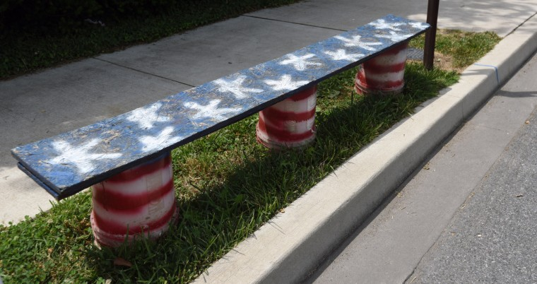 A bench painted in an American flag motif marks a spot along Frederick Road in advance of the 4th of July parade in Catonsville.  (Kim Hairston/Baltimore Sun)