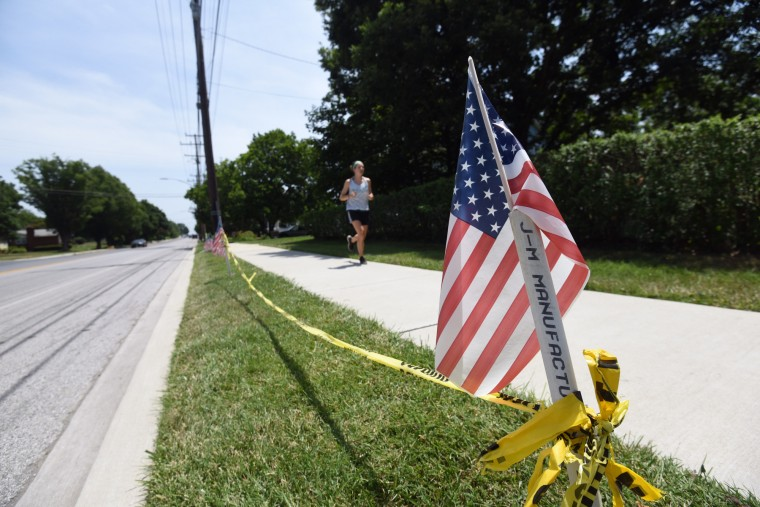 Caution tape strung between two American flags marks a spot along Frederick Road in advance of the 4th of July parade in Catonsville.   (Kim Hairston/Baltimore Sun)