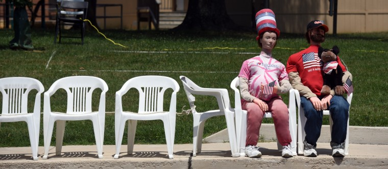 Two figures holding American flags and dressed in patriotic outfits hold seats on Frederick Road in advance of the 4th of July parade in Catonsville  (Kim Hairston/Baltimore Sun)