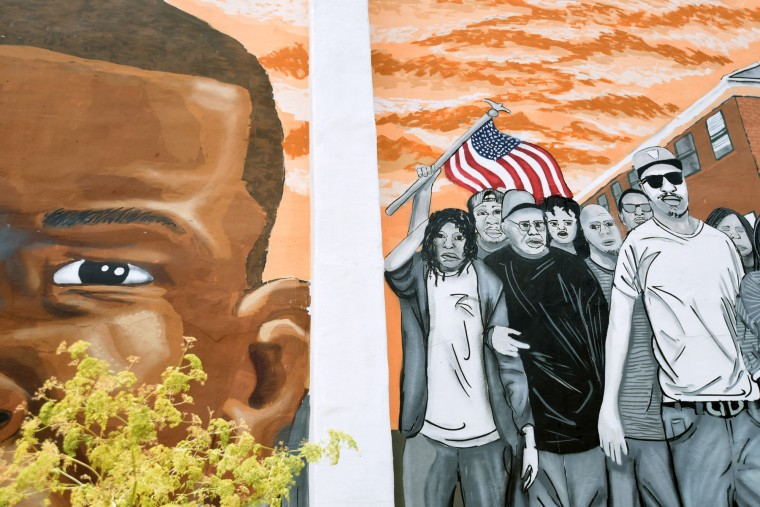 An American flag is seen in a detail of a mural by street artist  Justin Nethercut,  who goes by the name Nether.  On right, is an image of Freddie Gray and, on left, his family and friends. The three panel mural, on the corner of Mount and Presbury Streets, is near where Gray was arrested.  (Kim Hairston/Baltimore Sun)