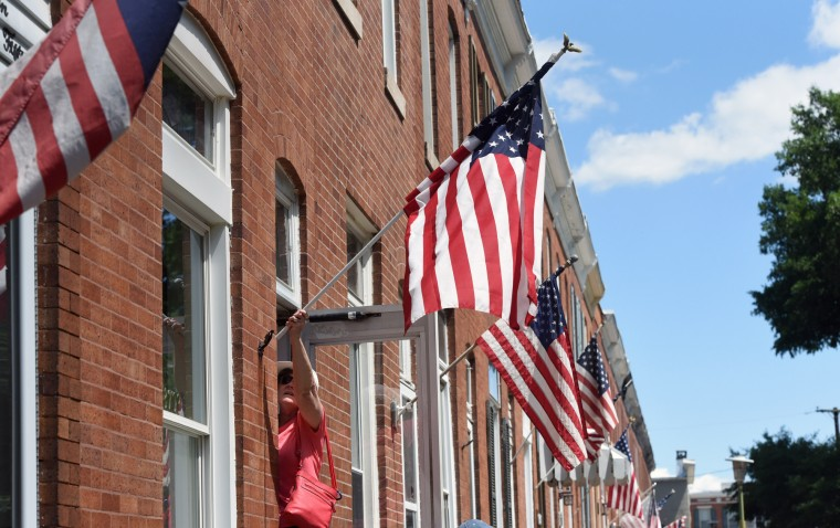 """Helen Bianca hangs an American flag outside of her home on Latrobe Park Terrace. Most of her neighbors in her Locust Point street display them. Bianca says """"Since 911 they've never really gone down."""" She brought her flag back out after wind and rain the night before.  (Kim Hairston/Baltimore Sun)"""