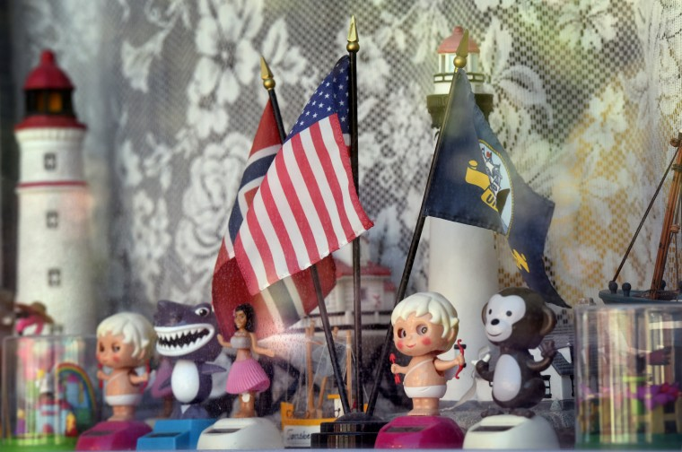 The flags of Norway, the United States of America and the United State Navy share a window in a home in the 1400 block of Hull Street with solar dancing toys, lighthouses and other items.  (Kim Hairston/Baltimore Sun)