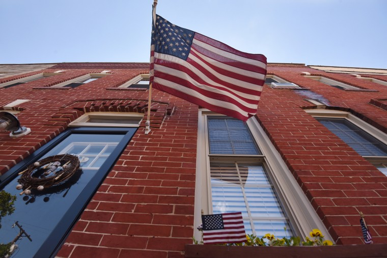 Several American flags are displayed outside a rowhouse in the 1300 block of Hull Street.  (Kim Hairston/Baltimore Sun)