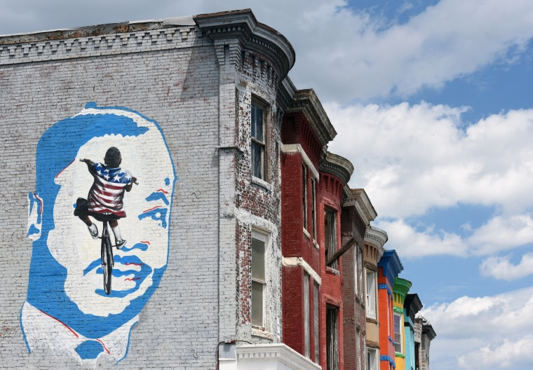 A mural over on W. North and Woodbrook Avenues over Phaze Two Barber Shop shows the likeness of Dr. Martin Luther King, Jr. and a young man wearing in a flag shirt.  (Kim Hairston/Baltimore Sun)