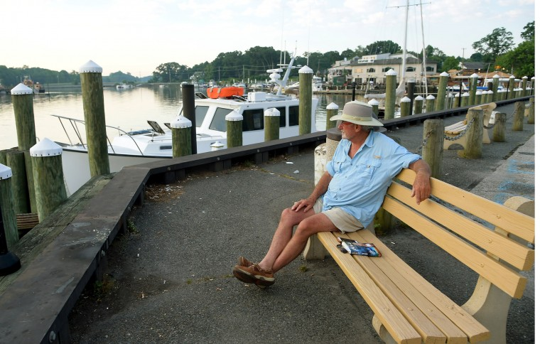 "Gerard Buckley, a delivery captain for the ""Sandpiper"" sailboat, sits on the dock by Pell Gardens as he waits for the tide to rise so he can depart. (Algerina Perna/Baltimore Sun)"