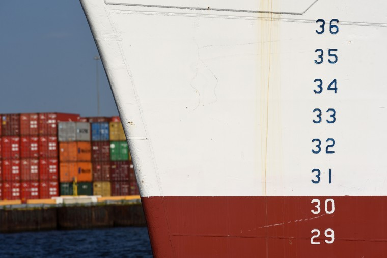 Containers stacked at Seagirt Marine Terminal can be seen in the distance behind the N.S. Savannah's bow, inscribed with depth markings. (Amy Davis/Baltimore Sun)