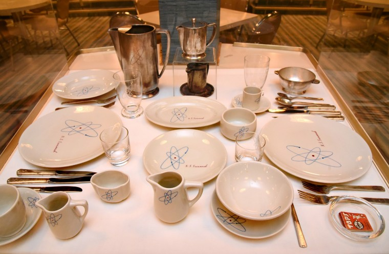 The serving ware on display in the dining room has an atom motif and the ship's name. T (Amy Davis/Baltimore Sun)
