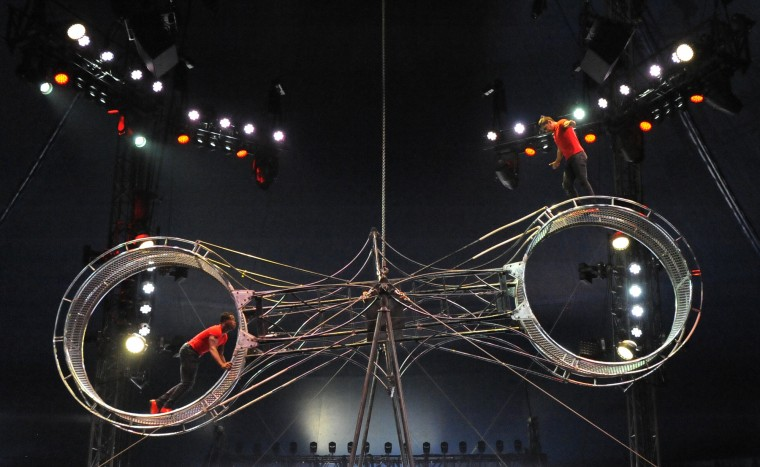 Performers on a giant steel wheel run and jump while the wheel spins under the big top.  (Lloyd Fox/Baltimore Sun)