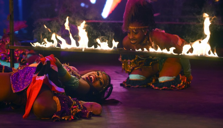 Members of the Caribbean Dynasty limbo under a bar of fire at the UniverSoul Circus. (Lloyd Fox/Baltimore Sun)