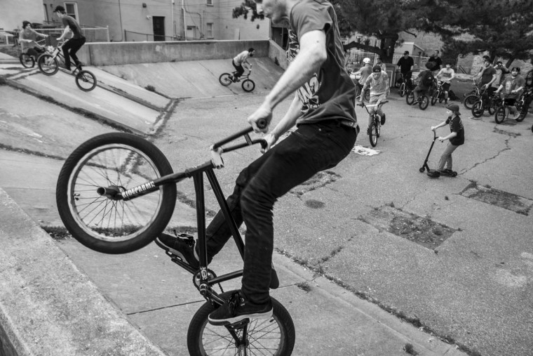 Baltimore, MD -- 5/27/17 -- BMX riders freestyle tricks at second location the day. Second Annual Baltimore BMX Street Jam. Over 150 BMX bike riders gathered on 300 North Greene street, Baltimore. Together they spent the whole day riding through the streets of Baltimore and exploring places that were once hidden to many riders. (Paul Lai)