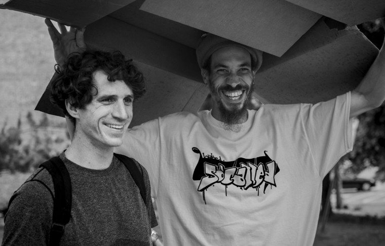 Baltimore, MD -- 5/27/17 -- Andrew Mick (left), Ian Burke (right) both smiling underneath a cardboard box, hiding from the rain. Second Annual Baltimore BMX Street Jam. Over 150 BMX bike riders gathered on 300 North Greene street, Baltimore. Together they spent the whole day riding through the streets of Baltimore and exploring places that were once hidden to many riders. (Paul Lai)