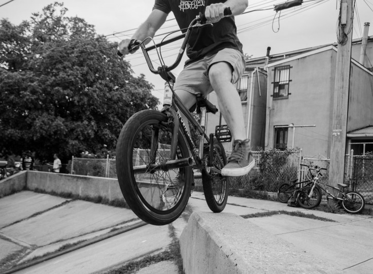 "Baltimore, MD -- 5/27/17 -- BMX rider performs a ""stall', balancing with only his back wheel on top of a ledge. Second Annual Baltimore BMX Street Jam. Over 150 BMX bike riders gathered on 300 North Greene street, Baltimore. Together they spent the whole day riding through the streets of Baltimore and exploring places that were once hidden to many riders. (Paul Lai)"