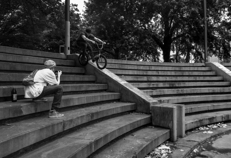 "Baltimore, MD -- 5/27/17 -- Ian Burke (left), photographs David Zovko (right), as he performs the trick, ""Feeble Grind down to a Manual ride off"". Second Annual Baltimore BMX Street Jam. Over 150 BMX bike riders gathered on 300 North Greene street, Baltimore. Together they spent the whole day riding through the streets of Baltimore and exploring places that were once hidden to many riders. (Paul Lai)"