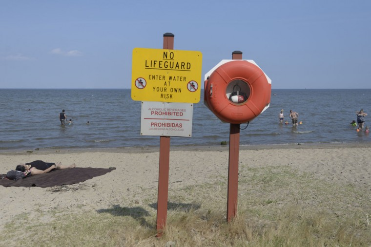 "There's no lifeguard on duty at North Point, so it's strictly ""swim at your own risk."" That hadn't deterred many beachgoers from taking a dip in the Chesapeake Bay. (Christina Tkacik/Baltimore Sun)"