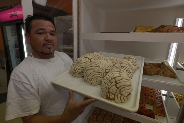 """Alberto Lesner with a sheet of conchas, a type of Latin American sweet bread, which he sells at his shop on Eastern Avenue in Highlandtown. The shop, one of several Latin """"panaderias"""" in the neighborhood, sells a variety of El Salvadoran and Mexican treats. (Christina Tkacik/Baltimore Sun)"""