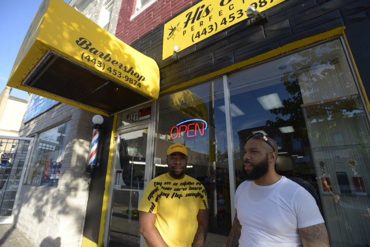 """Devin Fowlkes, left, manager His & Her Perfections Barbershop, praised the diversity of the neighborhood. """"Like me, I'm Afro-Latino."""" (Christina Tkacik/Baltimore Sun)"""