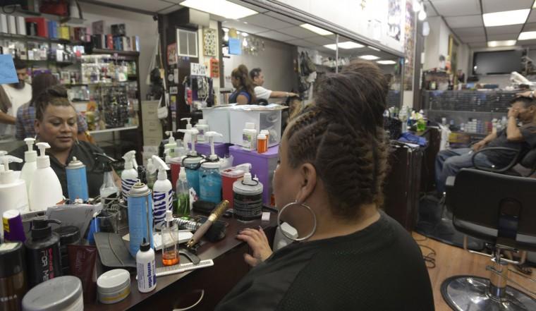 A stylist takes a break at Castillo & Villegas, one of the many salons in Highlandtown. (Christina Tkacik/Baltimore Sun)