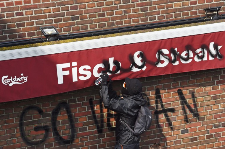 """A protester sprays """"Go Vegan"""" on a fish and steak shop on July 7, 2017 in Hamburg, northern Germany, where leaders of the world's top economies gather for a G20 summit.Protesters clashed with police and torched patrol cars in fresh violence ahead of the G20 summit, police said. German police and protestors had clashed already the day before at an anti-G20 march, with police using water cannon and tear gas to clear a hardcore of masked anti-capitalist demonstrators, AFP reporters said. / (AFP Photo/Christof Stache)"""