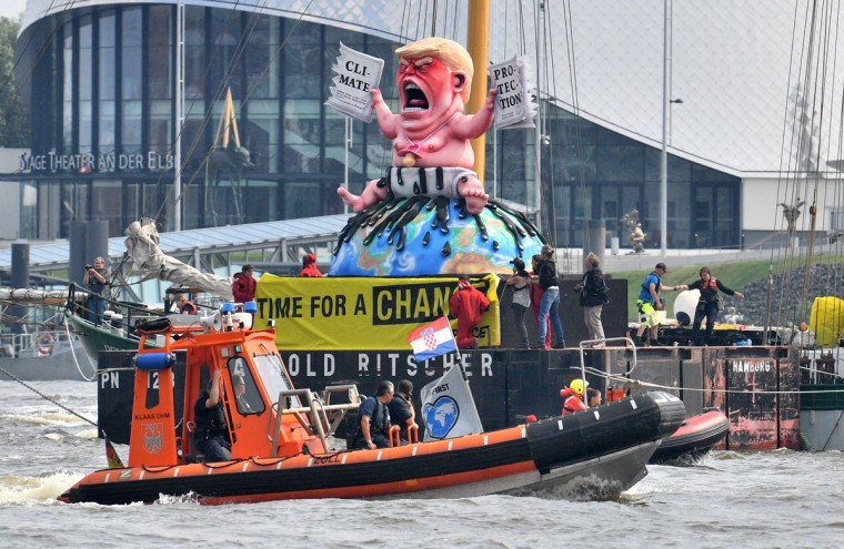 Greenpeace activists protest on a boat with a giant figure featuring US President Donald Trump as a baby, tearing up a climate protection document, on July 7, 2017 in Hamburg, northern Germany, where leaders of the world's top economies gather for a G20 summit.Protesters clashed with police and torched patrol cars in fresh violence ahead of the G20 summit, police said. German police and protestors had clashed already on Thursday (July 6, 2017) at an anti-G20 march, with police using water cannon and tear gas to clear a hardcore of masked anti-capitalist demonstrators, AFP reporters said. / (AFP Photo/Dpa / )