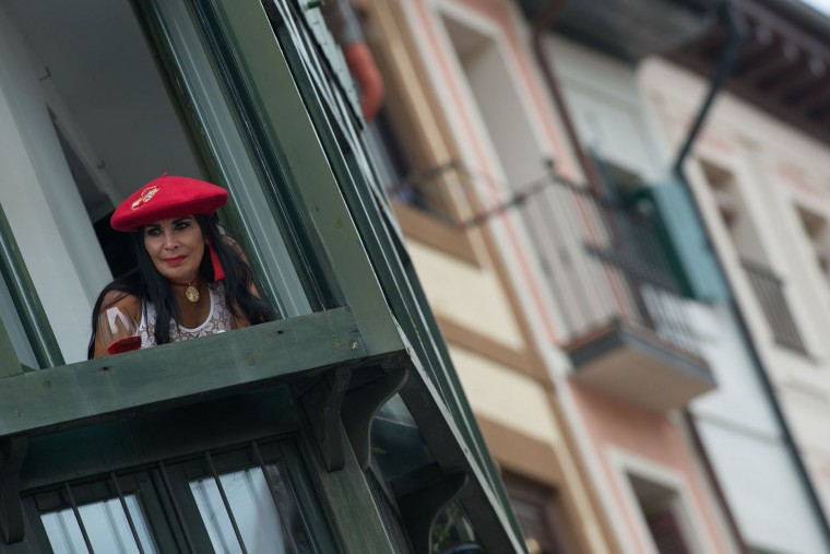 A woman sporting the typical red beret looks from a window as revellers celebrate the 'Chupinazo' (start rocket) at Pamplona's city-hall square, marking the kickoff at noon sharp of the San Fermin Festival, in front of the Town Hall of Pamplona, northern Spain, on July 6, 2017. A red-and-white sea of revellers soaked each other with wine in a packed Pamplona square today to kick off Spain's most famous fiesta, the San Fermin bull-running festival. (Miguel Riopa/AFP/Getty Images)