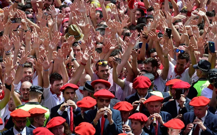 "Revellers dance as the ""Pamplonesa"" municipal music band performs during the launch of the 'Chupinazo' (start rocket) to mark the kickoff at noon sharp of the San Fermin Festival, in front of the Town Hall of Pamplona, northern Spain, on July 6, 2017. A red-and-white sea of revellers soaked each other with wine in a packed Pamplona square today to kick off Spain's most famous fiesta, the San Fermin bull-running festival. (Miguel Riopa/AFP/Getty Images)"