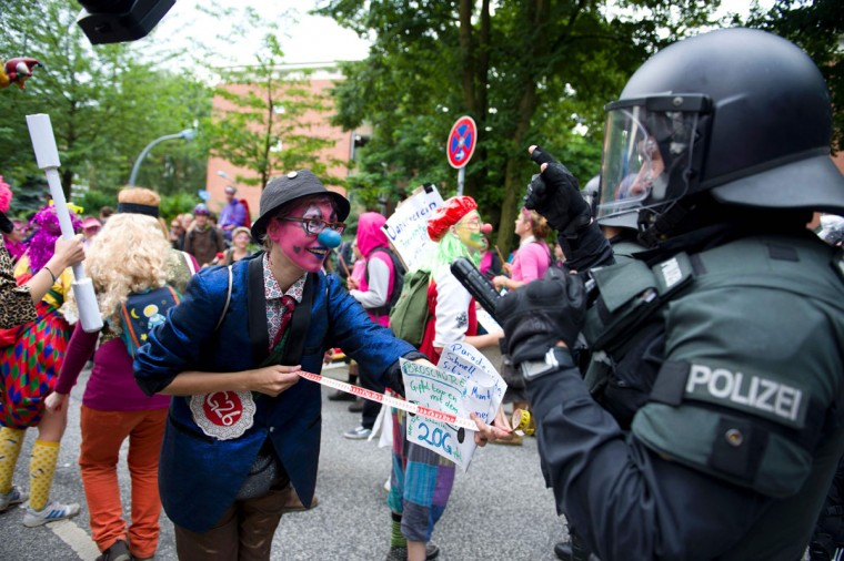 """Demonstrators dressed as clowns face policemen as they take part in a protest titled """"#BlockG20 - Color the Red Zone"""" on July 7, 2017 in Hamburg, northern Germany, where leaders of the world's top economies gather for a G20 summit.Protesters clashed with police and torched patrol cars in fresh violence ahead of the G20 summit, police said. German police and protestors had clashed already on Thursday (July 6, 2017) at an anti-G20 march, with police using water cannon and tear gas to clear a hardcore of masked anti-capitalist demonstrators, AFP reporters said. / (AFP Photo/Dpa / )"""