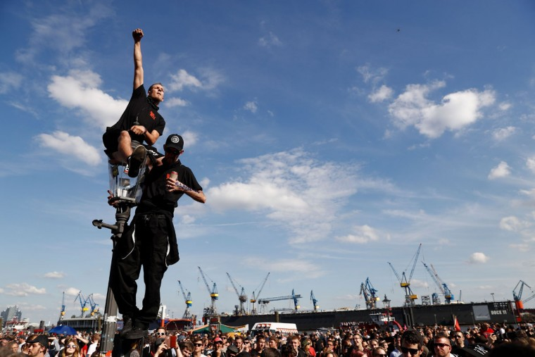 """Protesters listen to live music during the """"Welcome to Hell"""" rally against the G20 summit in Hamburg, northern Germany on July 6, 2017. Leaders of the world's top economies will gather from July 7 to 8, 2017 in Germany for likely the stormiest G20 summit in years, with disagreements ranging from wars to climate change and global trade. / (AFP Photo/Odd Andersen)"""
