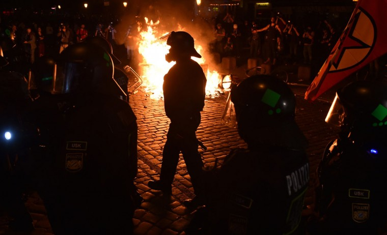 """Police officers walk in front of a fire started by protesters the """"Welcome to Hell"""" rally against the G20 summit in Hamburg, northern Germany on July 6, 2017. Leaders of the world's top economies will gather from July 7 to 8, 2017 in Germany for likely the stormiest G20 summit in years, with disagreements ranging from wars to climate change and global trade. / (AFP Photo/Christof Stache)"""