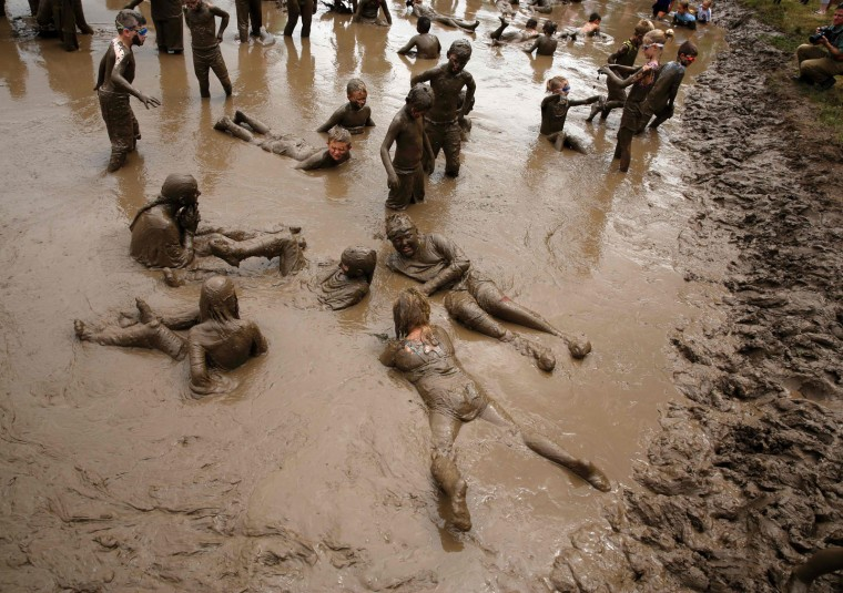 Kids play in the pit at Wayne County's annual Mud Day at Nankin Mills Park on July 11, 2017 in Westland, Michigan. The mud pit contains 200 tons (181 metric tons) of top soil and 20,000 gallons (75,708 liters) of water. (Jeff Kowalsky/AFP/Getty Images)