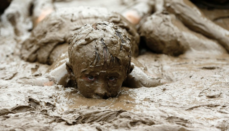 Kalie Weening of Ypsilanti, Michigan plays in the pit at Wayne County's annual Mud Day at Nankin Mills Park on July 11, 2017 in Westland, Michigan. The mud pit contains 200 tons (181 metric tons) of top soil and 20,000 gallons (75,708 liters) of water. (Jeff Kowalsky/AFP/Getty Images)