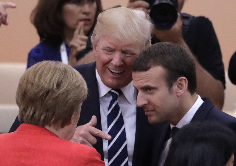 German Chancellor Angela Merkel, front, talks with U.S. President Donald Trump, centre, and France's President Emmanuel Macron prior to the first working session on the first day of the G-20 summit in Hamburg, northern Germany, Friday, July 7, 2017. The leaders of the group of 20 meet July 7 and 8. (AP Photo/Markus Schreiber)