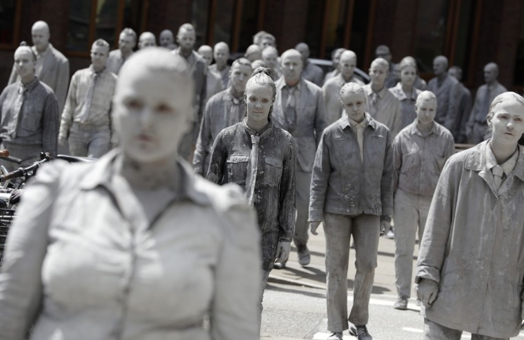 The performance '1000 GESTALTEN' with hundreds of people painted like clay figures move slowly and silently through the streets of Hamburg to protest against the G-20 summit in Hamburg, northern Germany, Wednesday, July 5, 2017. The leaders of the group of 20 meet July 7 and 8. (AP Photo/Matthias Schrader)