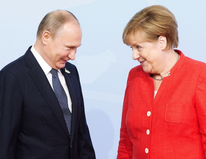 Russian President Vladimir Putin is greeted by German Chancellor Angela Merkel at the official welcoming ceremony at the G20 summit Friday, July 7, 2017 in Hamburg, Germany. (Remiorz/The Canadian Press via AP)