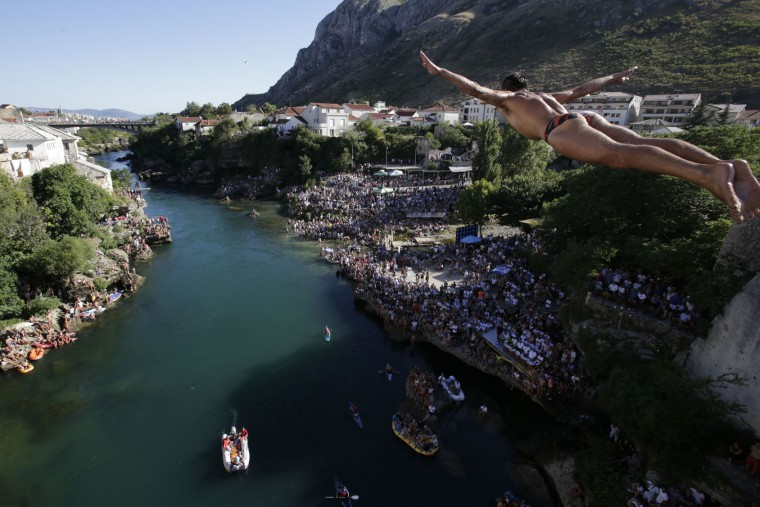A diver drops through the air from the Mostar bridge during traditional jump during 451th traditional annual high diving competition, in Mostar, 140 kms south of Bosnian capital of Sarajevo, Sunday, July 30, 2017. Total of 41 divers from Bosnia and neighbouring countries competed diving from 25 meters high Old Mostar Bridge into the Neretva river. (AP Photo/Amel Emric)