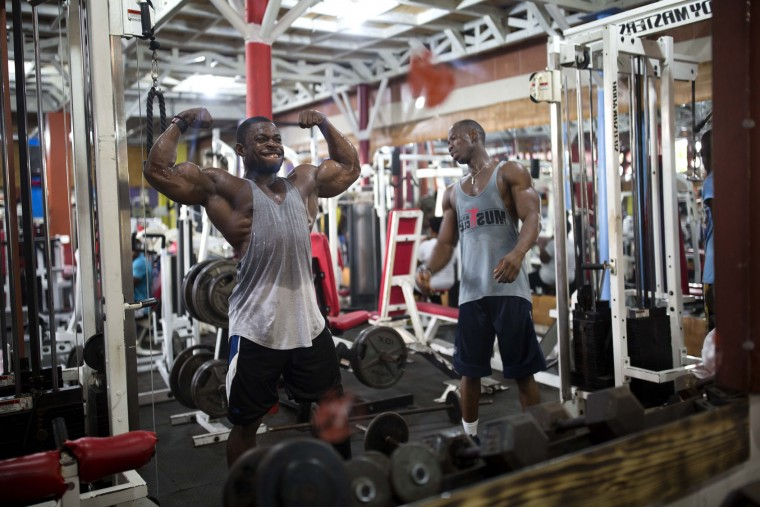 In this July 20, 2017 photo, bodybuilder Spely Laventure flexes his muscles in the mirror as he trains for an upcoming competition in Port-au-Prince, Haiti. Laventure gets to work out for free thanks to the owner of the local gym in Haiti's capital. (AP Photo/Dieu Nalio Chery)