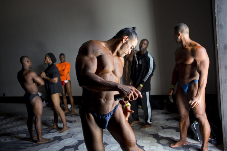 In this July 23, 2017 photo, Dominican Republic bodybuilder Jose Solano prepares backstage with other competitors before a competition between Haiti and Dominican Republic, in Port-au-Prince, Haiti. Sunday's event was organized by the Dominican bodybuilding federation and a Haitian bodybuilding group to generate support for the sport and make it more accessible in Haiti, where a handful of bodybuilders struggle to become professionals in a country where people make less than $2 a day. (AP Photo/Dieu Nalio Chery)
