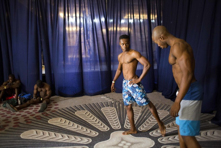 In this July 23, 2017 photo, Haitian bodybuilders Saintonge Pierre-Yves, right, and competitor Clement Whenael rehearse backstage for a bodybuilding competition between Haiti and Dominican Republic in Port-au-Prince, Haiti. Sunday's event was organized by the Dominican bodybuilding federation and a Haitian bodybuilding group to generate support for the sport and make it more accessible in Haiti, where a handful of bodybuilders struggle to become professionals in a country where people make less than $2 a day. (AP Photo/Dieu Nalio Chery)