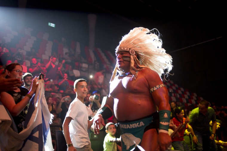 Wrestler Tatanka walks to the ring during The Rage Wrestling Mega Show in Tel Aviv, Israel, Sunday, July 9, 2017. The Israeli Wrestling League hosted a wrestling show in Tel Aviv with Kevin Von Erich and some of the WWE greatest of all time. (AP Photo/Ariel Schalit)