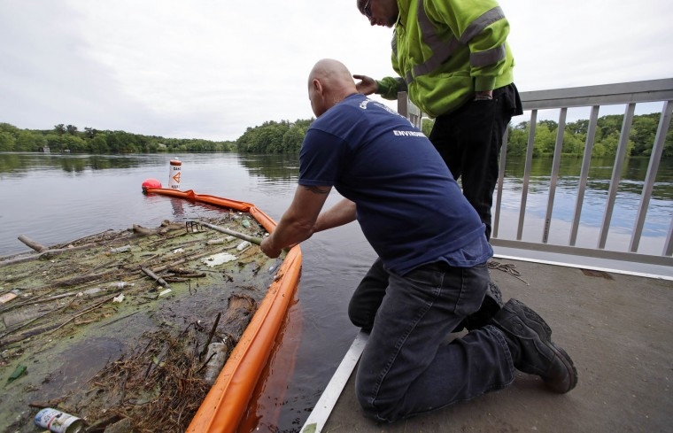 "In this Wednesday June 7, 2017 photo activist Rocky Morrison, left, of the ""Clean River Project"" examines a boom filled with waste collected from a recovery boat on the Merrimack River in Chelmsford, Mass. Morrison leads a cleanup effort along the Merrimack River, which winds through the old milling city of Lowell, and has recovered hundreds of needles in abandoned homeless camps that dot the banks, as well as in piles of debris that collect in floating booms he recently started setting. (AP Photo/Charles Krupa)"