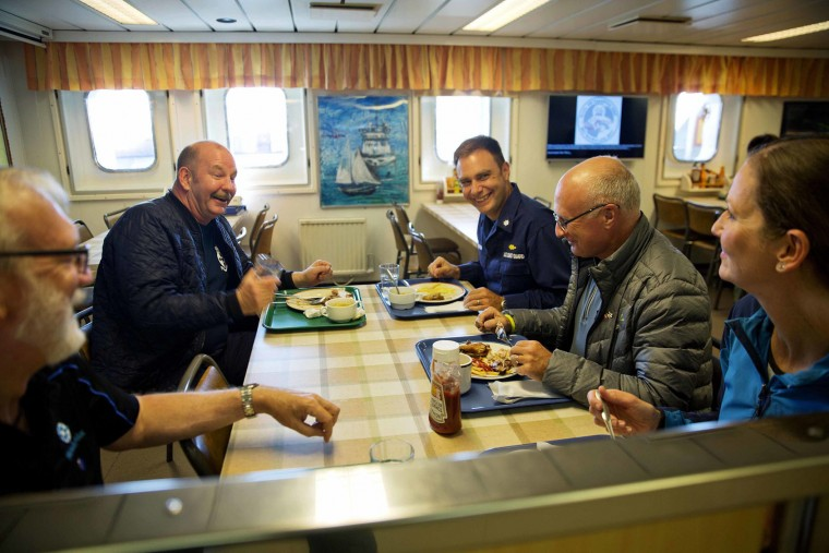 "In this Monday, July 10, 2017 photo, ice navigator Capt. David ""Duke"" Snider, from left, Canadian Coast Guard Capt. Victor Gronmyr, U.S. Coast Guard Cmdr. Bill Woityra, assistant ice navigator Nigel Greenwood, and biologist Paula von Weller talk over dinner in the mess hall aboard the Finnish icebreaker MSV Nordica as it sails the North Pacific Ocean to traverse the Northwest Passage through the Canadian Arctic Archipelago. (AP Photo/David Goldman)"